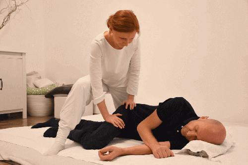 Tina Wieser-Walz, Shiatsu-Practitioner, beim Behandeln in Seitenlage (Gallenblasenmeridian am Bein).